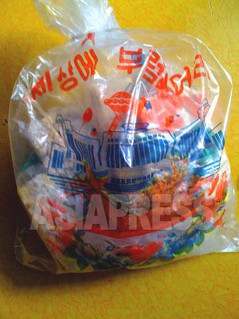 今年2月16日の金正日総書記の誕生日に配られた子供向け特別配給。菓子袋には「世に羨むものなし」と書かれ、平壌市にある「学生少年宮殿」の絵が描かれている。2011年2月 撮影 崔敬玉 (アジアプレス)