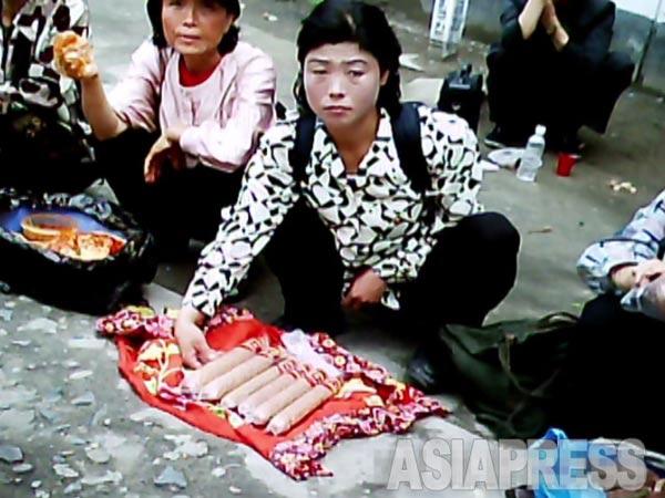 党大会取材のメディアは「発展する平壌」ばかりを報じさせられた。平壌でも庶民がたくましく商行為で生計を立てている。写真は中国製ソーセージを売る女性。2011年6月牡丹峰区域にてク・グァンホ撮影(アジアプレス)