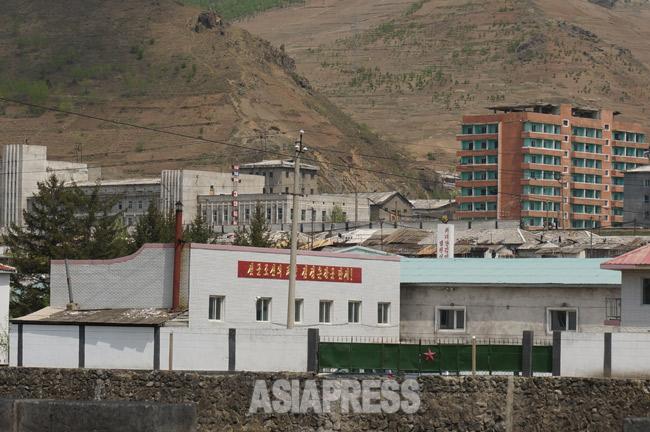荒廃した北朝鮮の山2 「先軍朝鮮の太陽金正恩将軍万歳」のスローガンが掲げられた建物の後ろに急勾配のはげ山が見える。2014年5月中旬、両江道恵山(ヘサン)市を中国側から撮影(アジアブレス)
