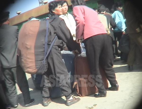 人が入るほど巨大なリュックを背負って駅のホームを移動する行商の二人組。2005年6月咸鏡南道咸興駅にてリ・ジュン撮影(アジアプレス)