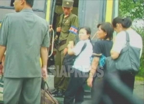 バスの昇降口に立ちはだかって平壌中心に向かう乗客の身分証を検査する兵士。国家安全 保衛部所属と思われる。2006年8月、撮影リ ・ジュン(アジアプレス)