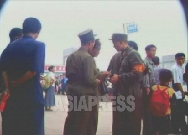 「警務」と呼ばれる憲兵が、軍人の身分証を 検査している。2006年8月、撮影リ・ジュン (アジアプレス)