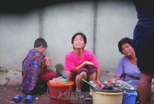 「食べて行きなさいよ」と撮影者に笑顔で声をかける冷麺売りの女性たち。2007年8月平壌市楽浪区域でリ・ジュン撮影(アジアプレス)