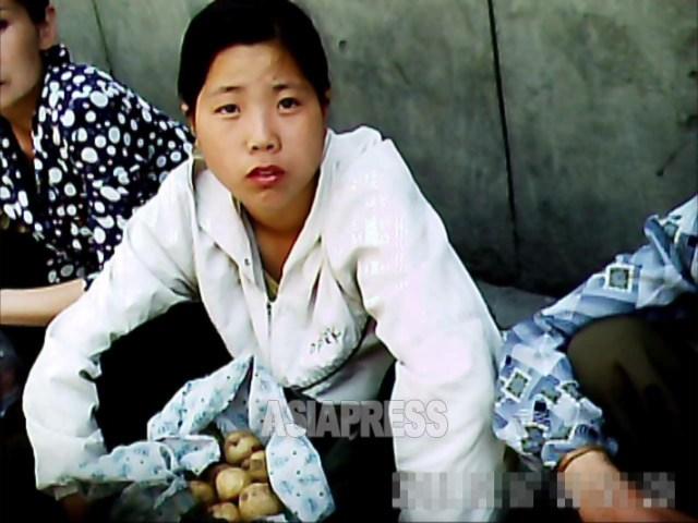 平壌中心部の牡丹区域のアパート街。座り込んでジャガイモを売る若い女性