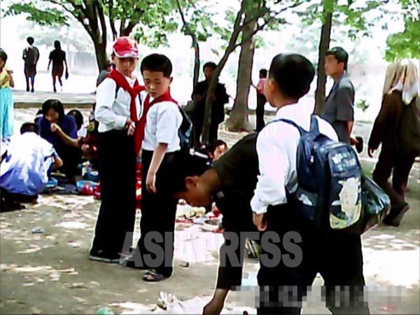 遠足に来た小学生たちが食事を終えた後、若い男性が残り物を漁り始めた。2011年6月平壌市大城区域にて、撮影ク・グァンホ(アジアプレス)
