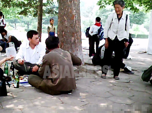 食事中のグループを老婆がじっと見つめながら食べ物を乞うている。2011年6月平壌市大城区域にて、撮影ク・グァンホ(アジアプレス)