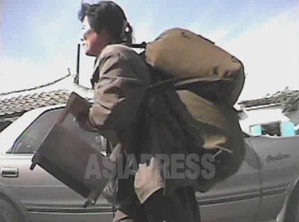 大きなリュックを二つ重ねで背負って市場に向かう女性。手に持つのは木製の椅子か。2008年10月黄海北道沙里院市にてシム・ウィチョン撮影(アジアプレス)