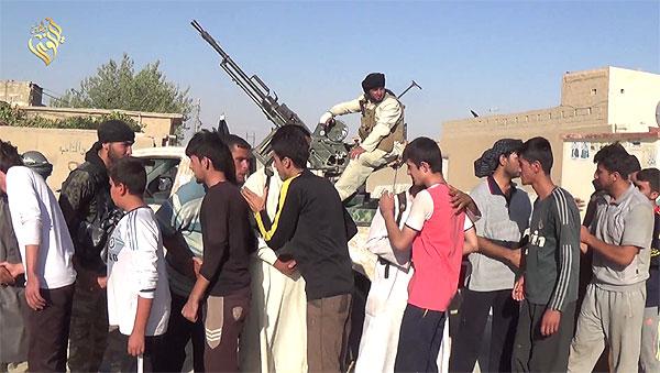 ISはシンジャル一帯を制圧すると、男性にイスラム教への改宗を迫り、拒否した者を殺害したりした。写真は「改宗したヤズディ住民を手厚く迎えるイスラム国兵士」としてISが公表したもの。この時女性たちは拉致されている。(IS映像)