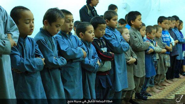 マンビジでは、家族とともにシリアに入った外国人戦闘員の子どもたちも多数暮らす。写真はISが「礼拝する子どもたちの様子」として伝えたもの。中央アジア系のように見える。(2015年IS写真)