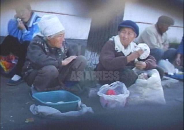 現金収入を得るため平壌市内のアパート街の路上で餅やパンなどを売る老人たち。2007年10月平壌市楽浪区域にてリ・ジュン撮影(アジアプレス)