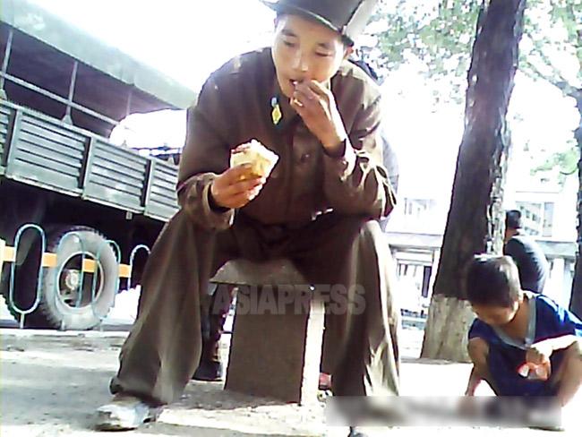「せめて油のひとさじでも出してくれたら」という下士官。見かねた撮影者が渡したパンにかぶりついた。すぐ脇では物乞いの子どもが落ちたパンくずを拾っている。2013年8月に北部地域で撮影。(アジアプレス)