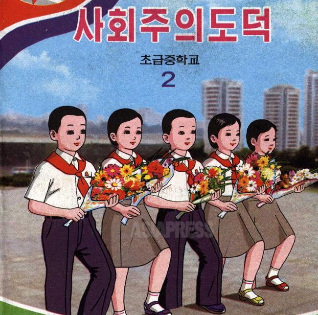 初級中学2年の「社会主義道徳」。花束を持った四人が金日成の銅像に献花に向かう姿を現した画だと思われる。表紙は愛らしいが、内容は権力者への忠誠教育一色だ。(アジアプレス)