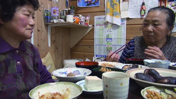 福島県伊達市の仮設住宅で。食卓には、避難先で借りた畑でつくった料理が並ぶ。とれたての新鮮な野菜のおいしさは忘れられないと古居監督は話す。(映画「飯舘村の母ちゃんたち 土とともに」より)