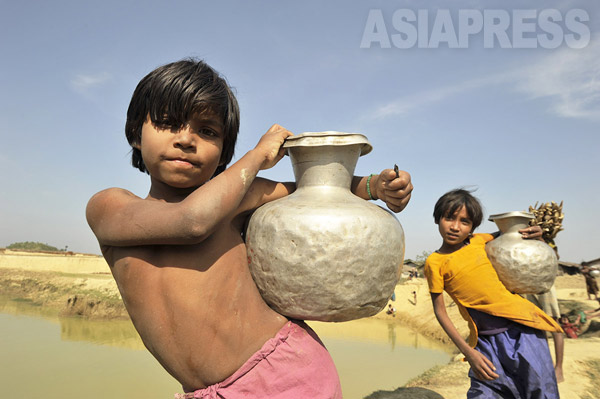 ミャンマーの隣国、バングラデシュの非公式キャンプの溜め池で水を汲むロヒンギャの子どもたち(撮影:宇田有三)