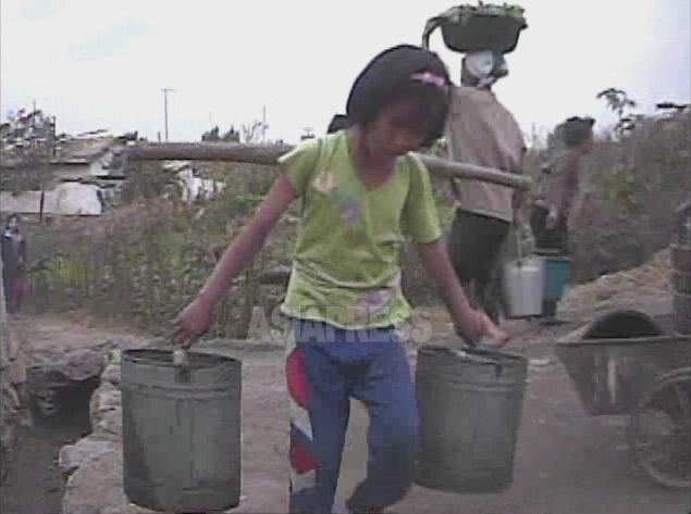 気合を入れて水満杯のバケツ二つつるした天秤棒を持ち上げた少女。2008年10月、黄海南道で撮影シム・ウィチョン(アジアプレス)