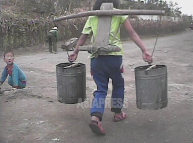 急いでいるのか、少女は背負子を負うて駆けて行った。2008年10月、黄海南道で撮影シム・ウィチョン(アジアプレス)