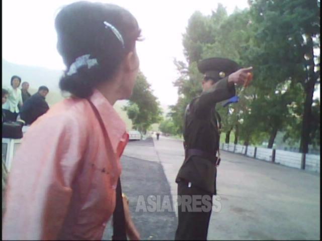 警官が検査のふりをして「サービ車」に近づき、何ごとか難癖をつけ始めた。2010年6月平安南道にて撮影キム・ドンチョル(アジアプレス)