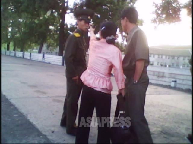 女性は若い警官を突き飛ばし「何様のつもりだ」と罵倒する。2010年6月平安南道にて撮影キム・ドンチョル(アジアプレス)