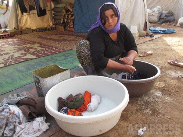 【シリア北東部】テントの前で洗濯をするヤズディ女性。ISが侵攻したため、家や土地も捨てざるを得なかった。(2014年9月撮影・玉本英子)