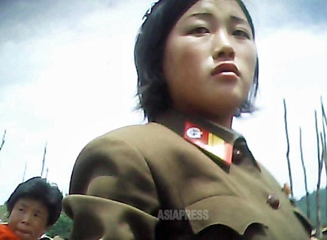 体格のいい女性兵士が路地の市場で買い物を していた。現在女性兵士の軍服務期間は7年だ。2013年6月両江道にて撮影「ミンドゥルレ」(アジアプレス)