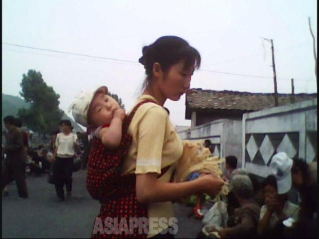 若い母親が赤ん坊を負ぶって買い物。2010年6 月平安南道で撮影キム・ドンチョル(アジアプ レス)