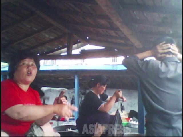でっぷり肥えた肉売りの女性が、しつこく値 切る男性客に「男のくせにみみっちい。アレ ついているのか」と毒舌。男性は耳をふさい でいる。市場は笑いに包まれた。2010年6月平 安南道で撮影キム・ドンチョル(アジアプレス )