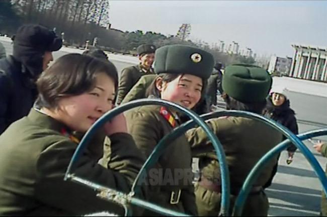 駅前で移動を待つ部隊の女性兵士たちが談笑している。辛い軍服務は7年にも及ぶ。冬用の綿入れを着てころころ。2012年11月 平安北道新義州(シニジュ)市にて撮影ペク・ヒャン(アジアプレス)