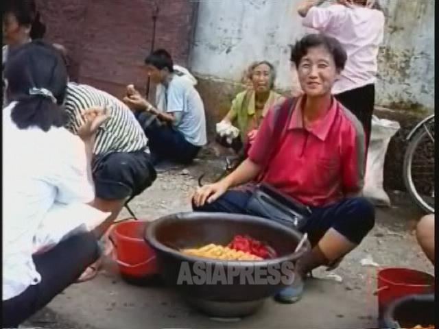 路地で「クァベギ」という揚げパンを売る女性。2007年8月黄海北道の沙里院(サリウォン)市にて撮影リ・ジュン(アジアプレス)