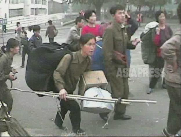 大荷物を持って開場する市場に急ぐ女性。 2008年10月黄海南道海州(ヘジュ)市にてシム ・ウィチョン撮影(アジアプレス)
