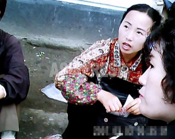 平壌中心部のアパート街。ばっちりメイクを決めて餅を売る女性。2010年7月平壌市モランボン区域にて撮影ク・グァンホ(アジアプレス)