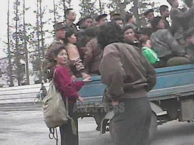 「サービ車」と呼ばれる乗合トラックに乗り込もうとするも場所がなくて戸惑う女性。2008年10月黄海南道海州(ヘジュ)市にて撮影シム・ウィチョン(アジアプレス)