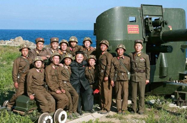 よれよれの軍服姿の兵士たちを見て、金正恩氏は何をおもっただろう? 記念撮影する金正恩氏。咸鏡南道の熊島(ウンド)の砲部隊で。2014年7月7日付労働新聞より引用