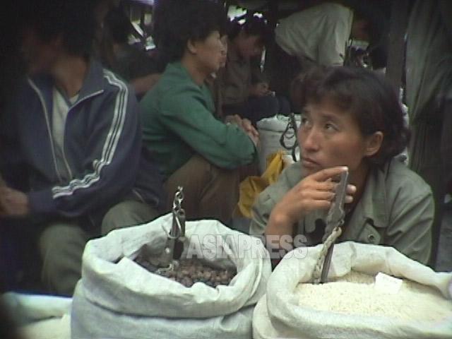 90年代半ば、国家によって厳しく供給統制されてきたコメが公然と闇市場で販売されるようになった。政治権力の無残な没落を象徴している。写真は江原道元山(ウォンサン)市の闇市場。1998年11月撮影アン・チョル(アジアプレス)