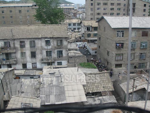 右に見えるアパートはブロックが積まれたままで外壁工事が未完なのに入居している。2008年6月平安南道にてペク・ヒャン撮影(アジアプレス)