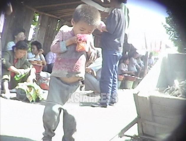 飢えたコチェビの男の子が、客の食べ残したソバの汁をビニール袋に入れてもらい食べている。1999年9月咸鏡北道茂山(ムサン)郡にて撮影キム・ホン(アジアプレス)