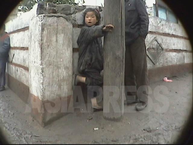 市場に立つ「コチェビ」の少女に男性が近寄 り話しかけている。無視する風の少女にしつ こく付きまとっていた。2004年7月清津市にて撮影リ・ジュン(アジアプレス)