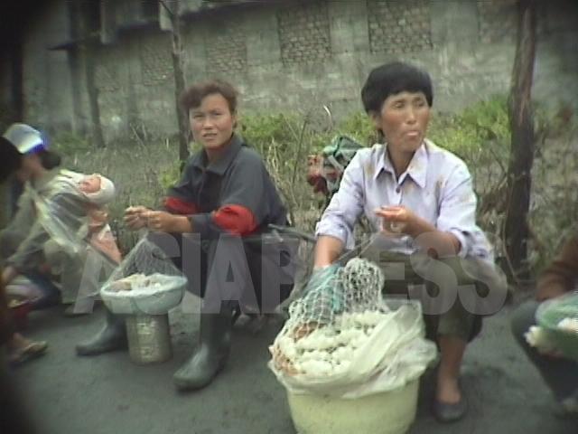 万引きと略奪から自衛するため、商人たちは商品にネットを被せるようになった。1998年10月江原道元山(ウォンサン)市にて撮影アン・チョル(アジアプレス)