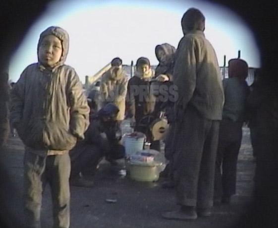闇市場の食べ物売りの周りに飢えた大人、子供のコチェビが集まっている。2000年3月清津(チョンジン)市にて撮影キム・ホン(アジアプレス)