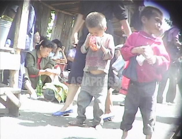 客の残したソバの残り汁をビニール袋に受けて食べる子供たち。全国の闇市場で見られた光景だ。1999年9月咸鏡北道の茂山(ムサン)郡にて撮影キム・ホン(アジアプレス)