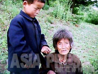 コチェビの取り締まりを避けるため、山中で暮らしている老婆と孫。境遇を嘆くおばあさんの話に、孫は涙にむせぶ。撮影ク・グァンホ(アジアプレス)
