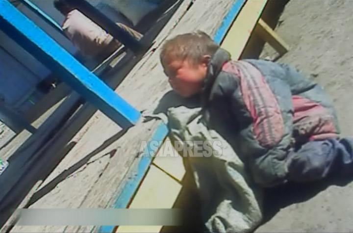 お腹が空いたためか疲れ果てたためか、10歳に満たないだろう男の子が市場でへたり込んでいた。2012年11月両江道恵山市郊外。両江道在住のアジアプレス取材協力者が撮影アジアプレス。