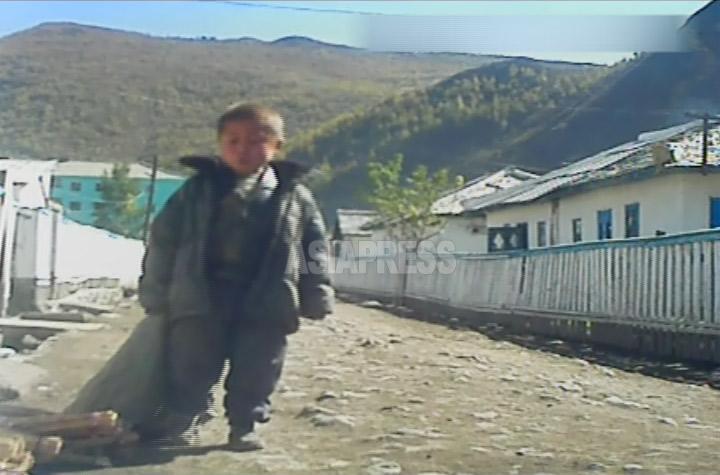 前の画像と同じ少年が、ずた袋を手にとぼとぼ歩いている。両親はいないの? と質問すると「いません」と短く答えた。2012年11月両江道恵山市郊外にて撮影アジアプレス。