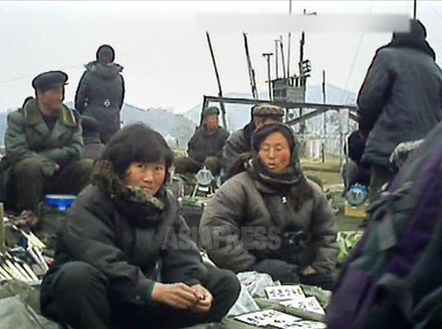 寒空の露天の市場で、手製の工具を売る女性。周囲の男性たちは退職した老人たち。2013年3月平安南道平城市にて撮影アジアプレス