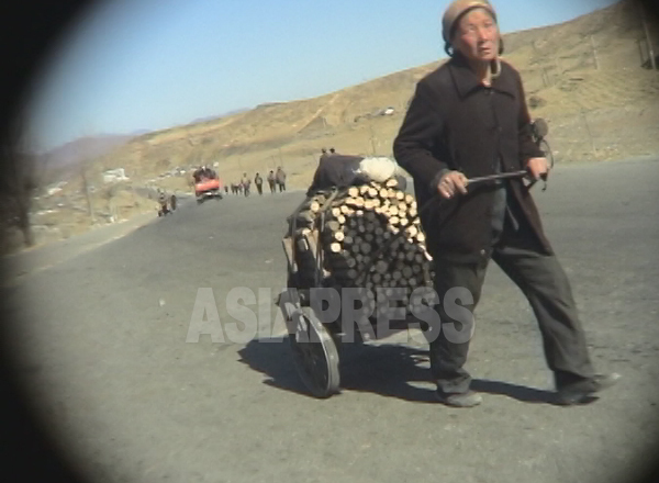 山で切った木を薪にして都市に運ぶ農村の老女。10数キロの道のりをリアカーで引いて来たという。2005年4月清津市にてリ・ジュン撮影(アジアプレス)