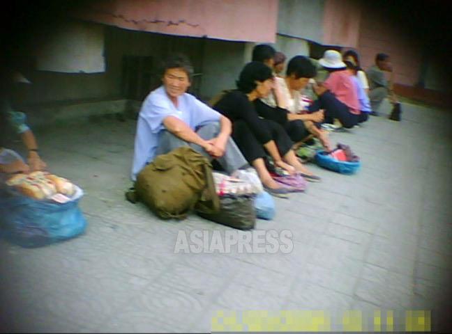 座り込んでパンや餅などの食品を売る女性たち。平壌中心部でも一歩裏通りに入ると庶民たちが路上で商売をしている。2011年9月平壌市にて撮影ク・グァンホ(アジアプレス)