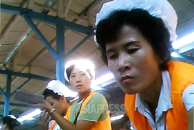 揃いの黄色のチョッキに衛生帽姿で公設市場で働く女性たち。彼女たちは雇われた店員ではなく幅80センチの売り場の経営者だ。2013年8月両江道恵山(ヘサン)市にて撮影アジアプレス