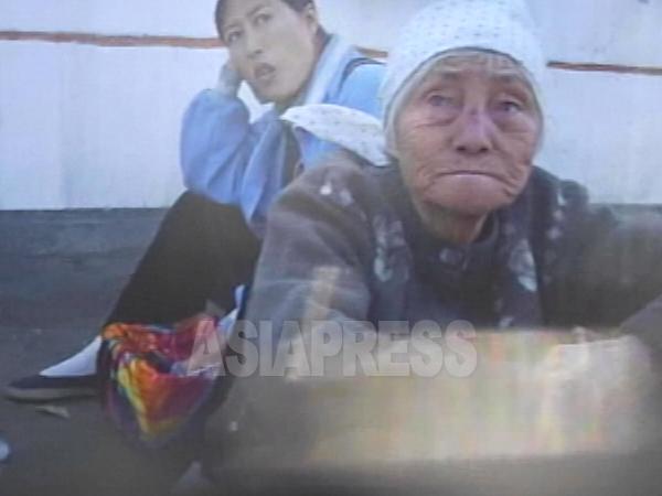 かなり高齢に見えるおばあさんが道端で食べ物を売っている。2007年10月平壌市楽浪区域にて撮影リ・ジュン(アジアプレス)