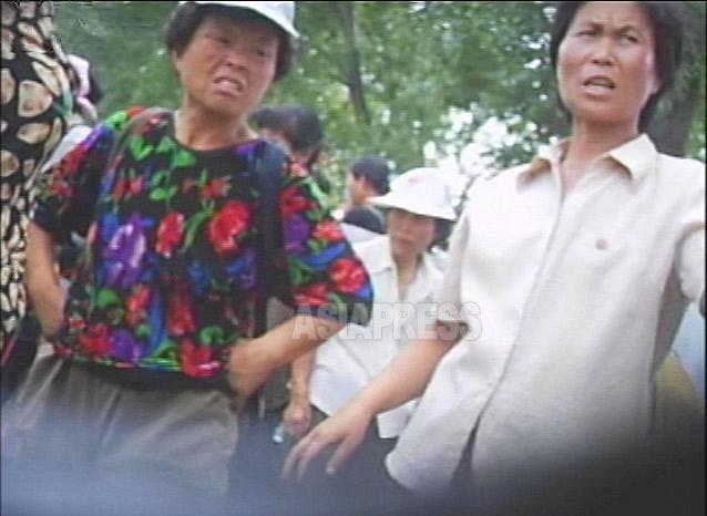 激しい形相の二人。公設市場の外で商売をしているところを取締り員に立ち退きを命じられ憤慨している。2007年8月平壌市力浦(リョッポ)区域にて撮影リ・ジュン(アジアプレス)