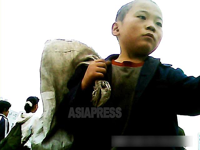 ずた袋を担いで街中を徘徊していた男の子。「髪が短く刈られているので孤児収容施設から逃げ出してきたのではないか」と撮影者。 2013年9月平安南道の平城市にて撮影アジアプレス