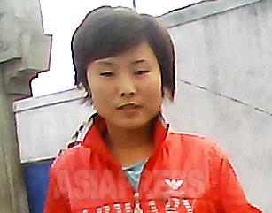 真紅のジャンパーがひと際目を引く女性。北朝鮮で流通する衣類の大部分は中国製。外部の文化が輸入品を通じて拡散していく。2013年9月咸鏡北道の清津市にて撮影アジアプレス